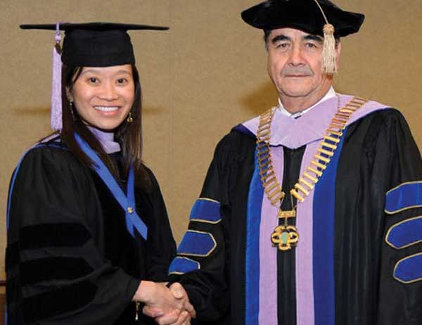 Christina Do is congratulated by President Ramon Baez