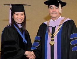 Christina Do is congratulated by President Ramon Baez